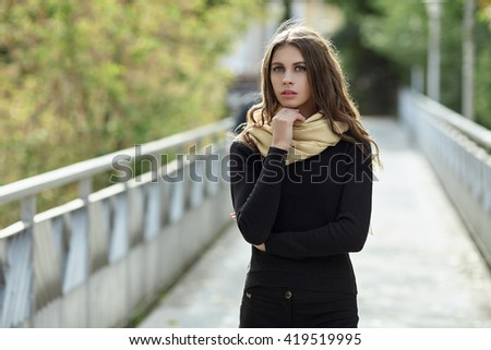 Outdoor portrait of young beautiful brunette woman with wavy long hair stares into camera posing on the park bridge