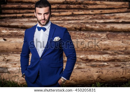 Outdoor portrait of young beautiful fashionable man against wood trunks as background.
