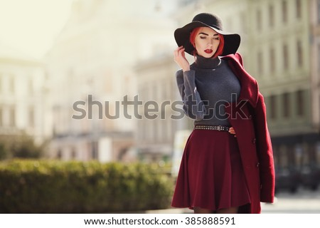Outdoor portrait of young beautiful fashionable woman posing at street of the old city. Model wearing stylish black wide-brimmed hat, red coat. Girl looking down. Female fashion. Copy space. Toned - stock photo
