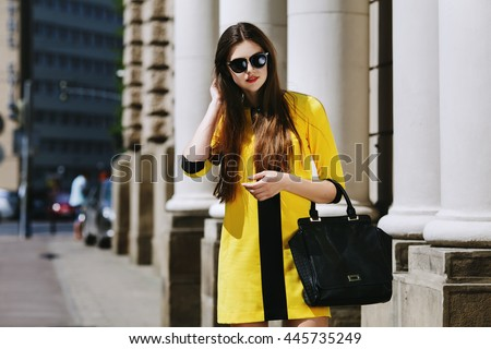 Outdoor portrait of young beautiful lady walking on the street. Model wearing sunglasses & stylish yellow summer dress. Girl looking down. Female fashion concept. City lifestyle. Sunny day. Waist up - stock photo