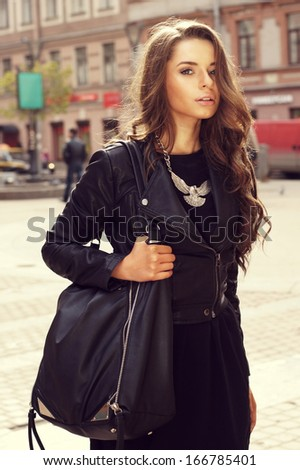 outdoor portrait of young beautiful stylish girl in black dress and jacket - stock photo