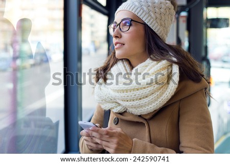 Outdoor portrait of young beautiful woman using her mobile phone on a bus. - stock photo