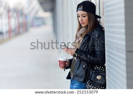 Outdoor portrait of young beautiful woman with mobile phone and coffee. - stock photo