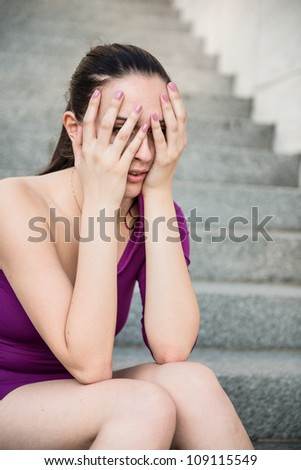 Outdoor portrait of young beautiful worried woman - hands on face - stock photo