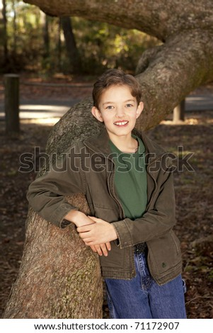 outdoor portrait of young boy and large oak tree - stock photo