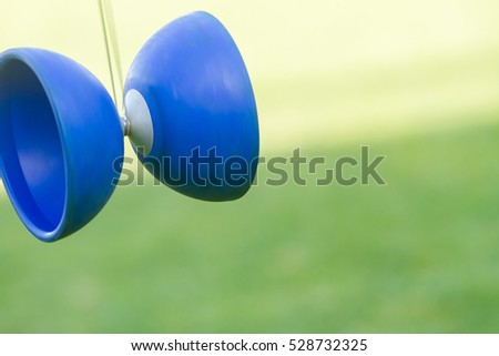 outdoor portrait of young boy playing with diabolo, chinese yo-yo toy
