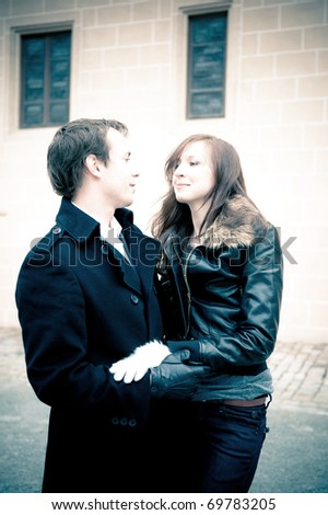 Outdoor portrait of young couple in love, soft blue tint - stock photo
