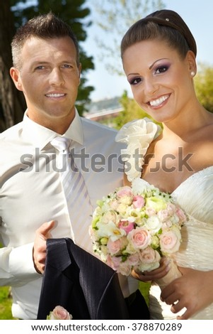 Outdoor portrait of young couple on wedding-day, smiling happy, looking at camera.
