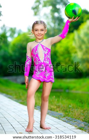 outdoor portrait of young cute little girl gymnast training with ball - stock photo
