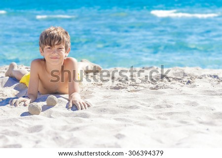 outdoor portrait of young european child boy enjoying summer vacation on beach on natural background - stock photo