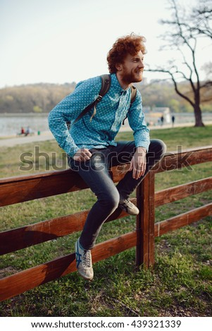 Outdoor portrait of young handsome smiling ginger man - stock photo