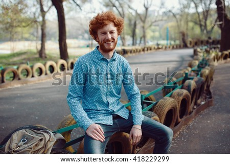 Outdoor portrait of young handsome smiling ginger man with beard - stock photo