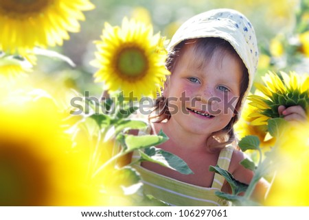outdoor portrait of young happy child girl in sunflower field