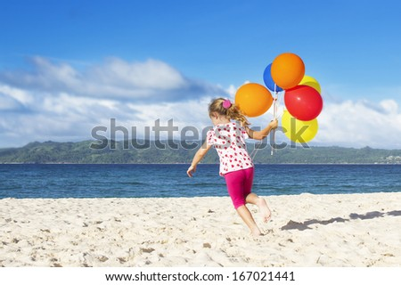 outdoor portrait of young happy girl running by sand beach on sea background with colorful balloons - stock photo