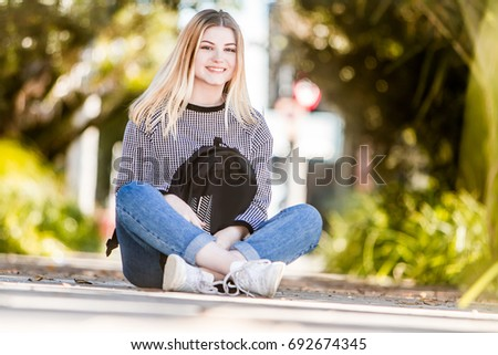outdoor portrait of young happy smiling teen girl on natural background on a sunny day