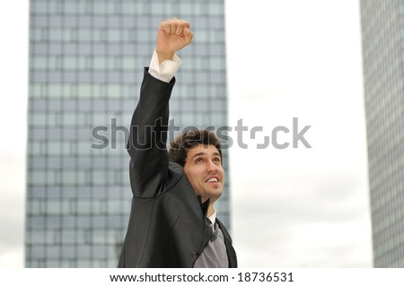 Outdoor portrait of young, happy  winner businessman with arms wide open - stock photo