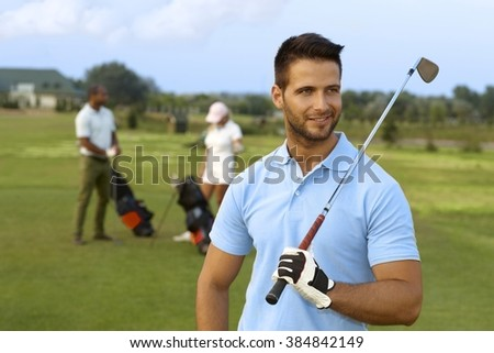 Outdoor portrait of young male golfer holding golf club, smiling, looking away.