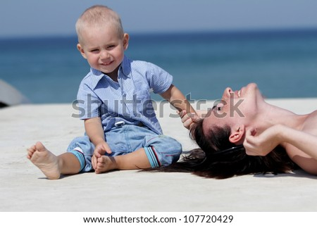 outdoor portrait of young mother and child on blue sky background - stock photo