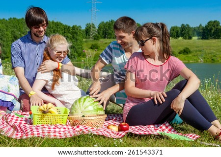 outdoor portrait of young people having a picnic, eat watermelon