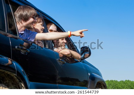 Outdoor portrait of young people looking out the window black ca - stock photo