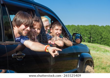 Outdoor portrait of young people looking out the window black car - stock photo