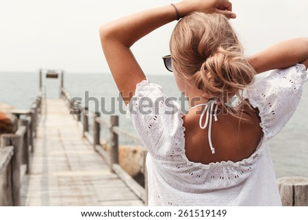 Outdoor portrait of young pretty blonde sexy tanned woman standing on the pier near the sea and waiting for somebody alone  - stock photo
