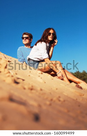 Outdoor portrait of young pretty couple in love in summer. Yellow sand and blue sky with copyspace.  - stock photo