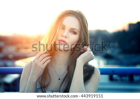 Outdoor portrait of young pretty sexy woman with sensual lips posing at roof at the end of bright sunset. Lovely soft back light.  - stock photo
