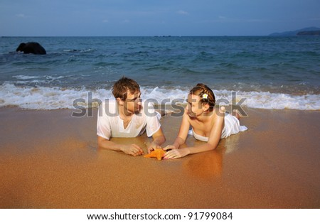 outdoor portrait of young romantic couple in white cotton clothes laying on evening beach with asteroid of Phuket island, Thailand - stock photo