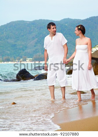 outdoor portrait of young romantic couple in white cotton clothes on beach of Phuket island, Thailand - stock photo