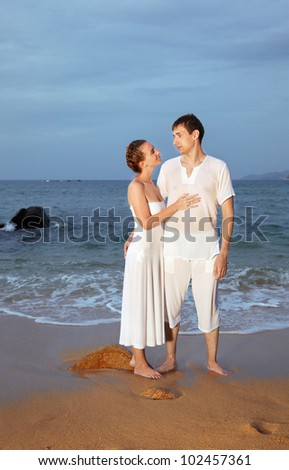outdoor portrait of young romantic couple in white cotton clothes on evening beach of Phuket island, Thailand - stock photo