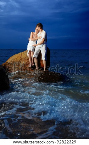 outdoor portrait of young romantic couple in white cotton clothes sitting on stone with waves around at night beach of Phuket island, Thailand - stock photo