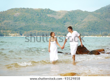 outdoor portrait of young romantic couple in white cotton clothes walking in waves at the beach of Phuket island, Thailand - stock photo