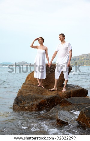 outdoor portrait of young romantic couple standing on stone in white cotton clothes among azure waters of Phuket island, Thailand - stock photo