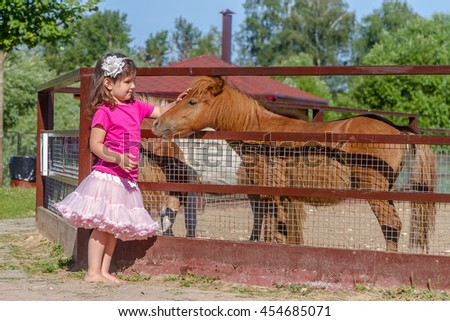 outdoor portrait of young smiling child girl feeding horse on farm - stock photo