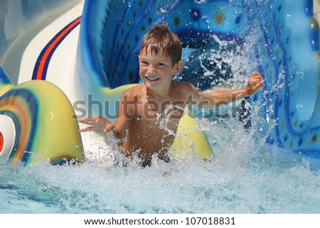 outdoor portrait of young smiling child having fun in aquapark - stock photo