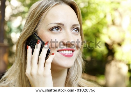Outdoor portrait of young woman talk on mobile telephone. - stock photo