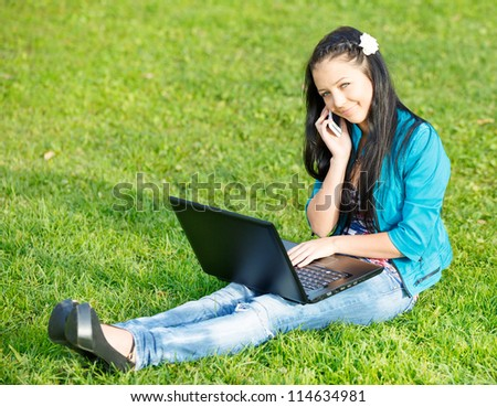 Outdoor portrait of young woman using a laptop - stock photo