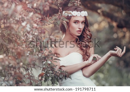 Outdoor portrait of young woman with a flower wreath