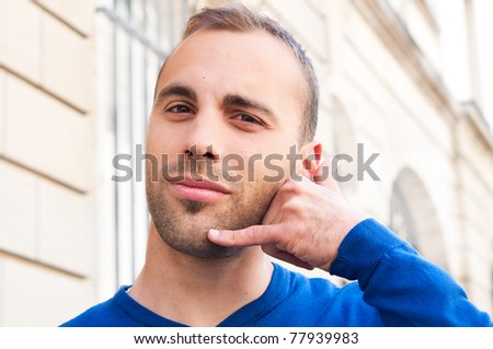 Outdoor portrait young men talk on a cellular telephone