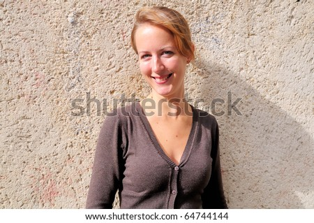 Outdoor portrait young woman with brick wall - stock photo