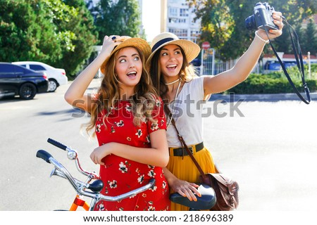 Outdoor portraits of two pretty girls friend taking selfie on vintage camera, enjoy nice day,welling with retro bikes, wearing elegant hats and dresses, looking on camera and making funny faces. - stock photo