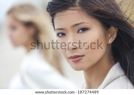 Outdoor profile portrait of a beautiful thoughtful Chinese Asian young woman or girl with blond female friend at beach - stock photo