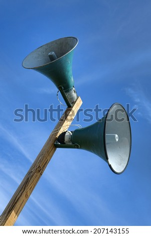 Outdoor public announcement communication system loudspeakers with horn speakers electronic sound amplification device mounted on a wood pole broadcasting a message at an event grounds - stock photo