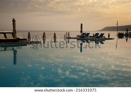 Outdoor resort pool with the reflection of the sky - stock photo
