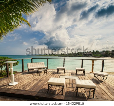 Outdoor restaurant at the beach. Cafe on the beach, ocean and sky. Table setting at tropical beach restaurant. Dominican Republic, Seychelles, Caribbean, Bahamas. Relaxing on remote Paradise beach. - stock photo