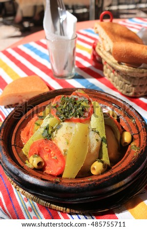 Outdoor restaurant dinner consisting of chicken and vegetables served in a earthenware tajine, in Morocco