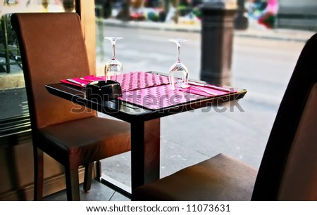 Outdoor restaurant in Paris, France, Europe. A table set for two person with an ashtray. - stock photo
