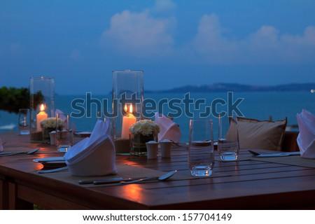 Outdoor restaurant table dinner setting on the beach at dusk - stock photo