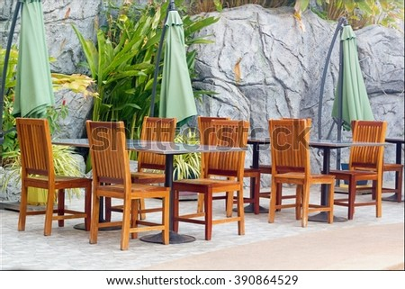 Outdoor restaurant with empty tables and chairs in garden landscape - stock photo